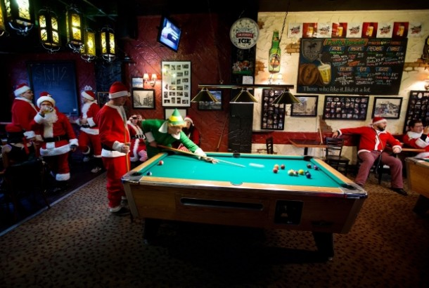 Santa playing pool with elf